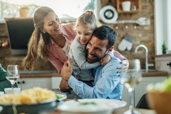 Young happy parents embracing with their small daughter during lunch at dining table.