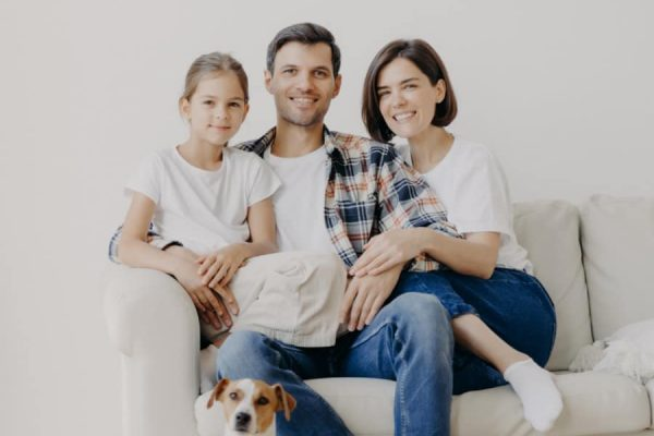 Horizontal view of three friendly family members and small pedigree dog pose at camera for making memorable photography. Dauther spends free time with mother and father, have good day at home
